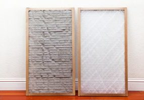 Old and New air conditioner filter next to each other leaning against the wall