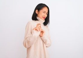 Young chinese woman wearing turtleneck sweater standing over isolated white background disgusted expression, displeased and fearful doing disgust face because aversion reaction. With hands raised. Annoying concept.
