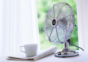 electric fan improving indoor air quality next to a newspaper