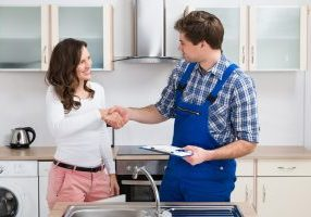 Young Woman Shaking Hands To Male Plumber With Clipboard In Kitchen to sign on for indoor plumbing in Bowling Green, Ohio